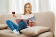 Relaxation. Good-looking alert young blond long-haired woman smiling and holding a glass of red wine and looking through a fashion magazine while sitting on the sofa