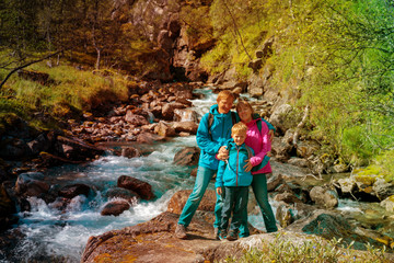 family with small kid travel hiking in nature of Norway