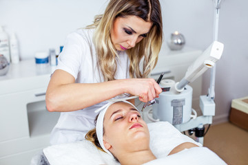 Cosmetologist is doing procedure for young girl. Procedure of Microdermabrasion. Model, close-up. Cosmetological clinic. Healthcare