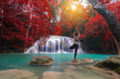 Young woman posture at the natural waterfall. Waterfall at colorful autumn forest.