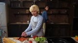 Healthy nutrition. Nice elderly woman cutting vegetables while cooking meal with her daughter in the kitchen - 185261764
