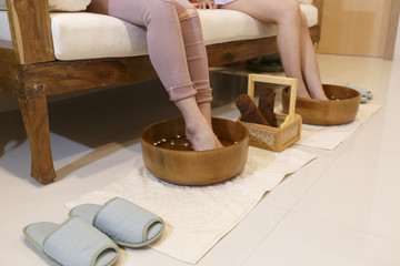 Two young women soaking feet in a bowl waiting spa staff to clean. woman feet in bowl of floral scented water in spa.