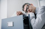 Tired office worker sleeping in the office - 185307304