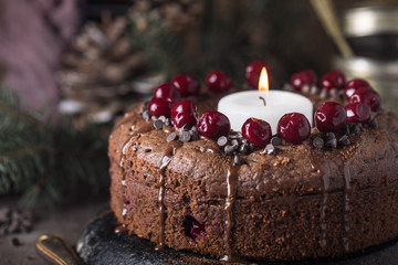 Double chocolate cherry cake with spices and big candle on the rustic background for winter holidays. Christmas and New Year decoration