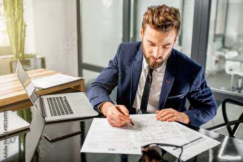 Foto Murales Handsome tax manager dressed in the suit working with documents and laptop at the modern office interior