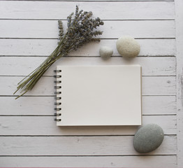 Lavender, stones and notebook on white wooden table with space for your text. © Katerina