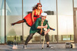 Woman jumps during a dance, she dances with an old man.