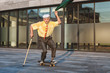 Playful grandfather is rolling on a skateboard, in his hand a jacket with which he is waving.