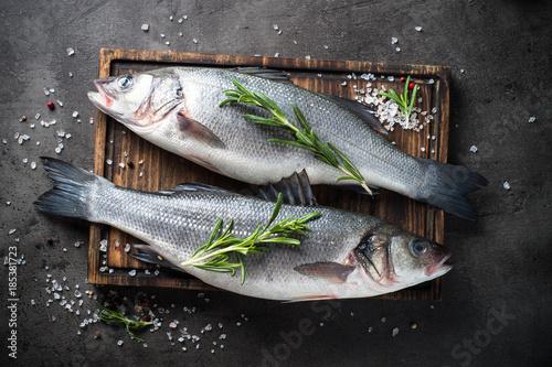 Foto Murales Fresh fish seabass on black background.