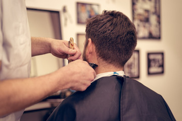 Young handsome man in barbershop