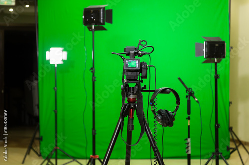 The camera on the tripod, led floodlight, headphones and a directional microphone on a green background. The chroma key. Green screen - 185389169