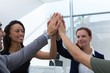Group of executives giving high five at office