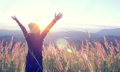 Leinwanddruck Bild Happy Woman Enjoying Nature on grass meadow on top of mountain cliff with sunset outdoor. Freedom concept.