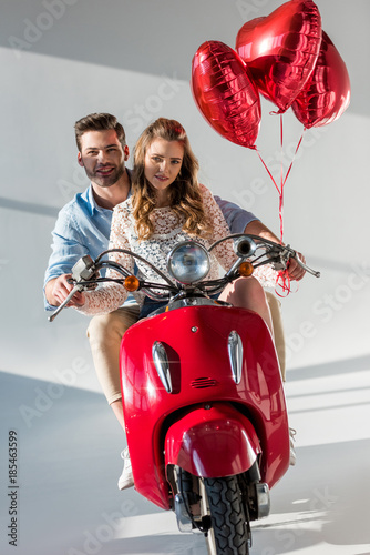 couple with red heart shaped balloons riding red scooter together Poster