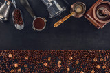 top view of roasted coffee beans with brown sugar and various coffee makers and grinders on black - 185466352