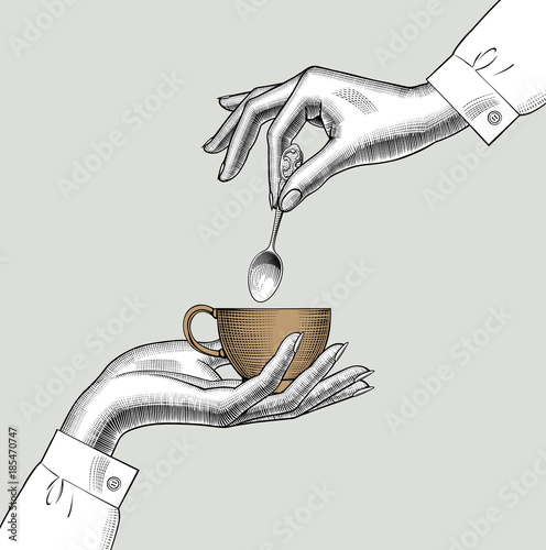 Pair of female hands with a coffee cup and spoon