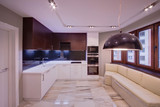 The light big kitchen with light and dark cases, a marble floor and a light sofa