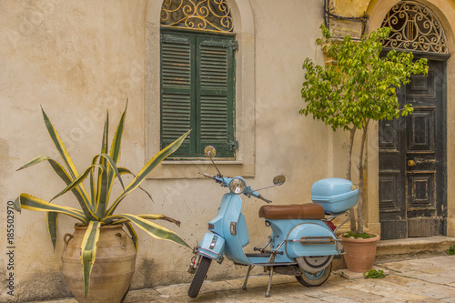 Foto op Canvas Scooter Corfu, Greece- December 21, 2017: Narrow streets and alleys in Corfu town Greece.Architecture in the old town of Corfu is heavily influenced my the Venetian architecture.Blue Vespa outside a building.