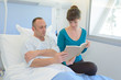 caring wife reading to his husband in hospital