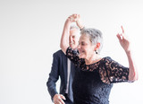 Close up of elegantly dressed older man and woman dancing exuberantly against neutral background (selective focus) - 185537922
