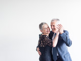 Mid length view of elegantly dressed older man and woman dancing against neutral background (selective focus) - 185537965