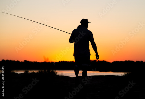 Silhouette of a man with a fishing rod at sunset - 185554375