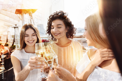Hen party. Happy cheerful delighted women holding glasses with champagne and cheering with them while having hen party