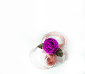 Purple flower with ribbon for decoration, isolated white background.