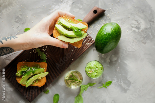 Woman holding delicious avocado toast over table, top view