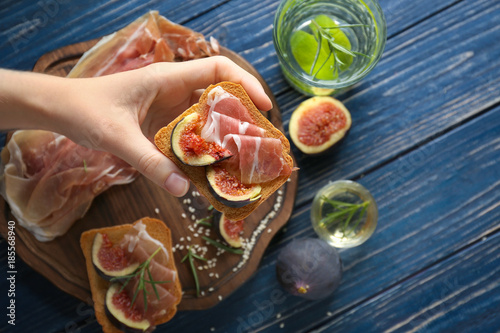 Woman holding delicious sandwich with lunch meat and fig over table, top view