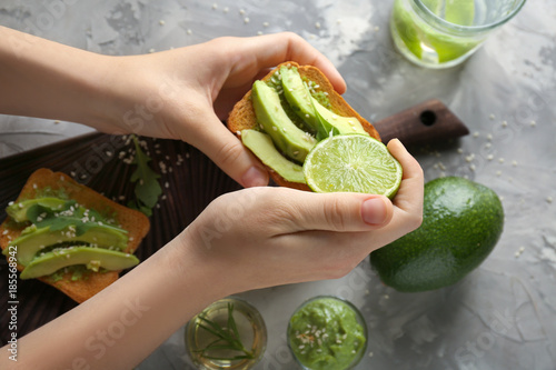 Woman preparing delicious avocado toast over table, top view