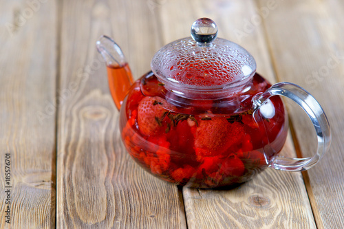 tea with raspberries and strawberries on wooden background