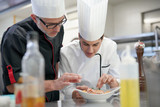 Professional cook chefs in kitchen improving dish composition - 185581146