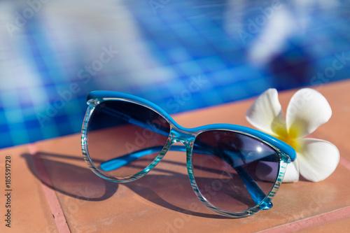 Aluminium Plumeria Blue sunglasses with plumeria, frangipani flower on border of a swimming pool
