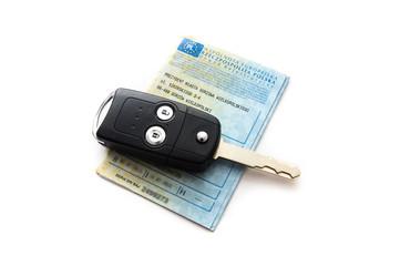 Dowód rejestracyjny i kluczyki do samochodu na białym tle.