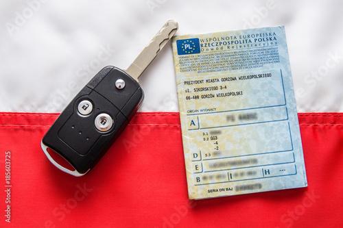 Dowód rejestracyjny i kluczyki do samochodu na tle flagi Polski.
