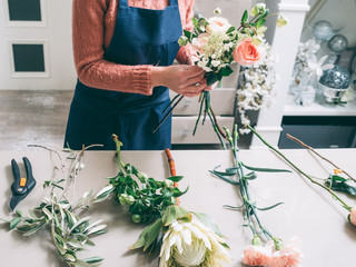 Florist's creative work requires senses of style beauty and proportion. Woman making beautiful flower arrangement from roses, dahlias, carnation