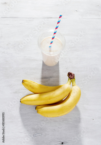 Aluminium Milkshake Milk banana cocktail on white wooden background, top view