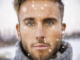 Headshot of handsome young man outdoor in winter fashion, wearing turtleneck sweater duriing snowfall