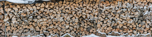 Foto op Aluminium Brandhout textuur Panorama of snowy firewood as a background or texture
