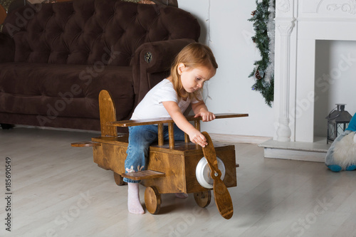 Little cute girl on a wooden toy plane