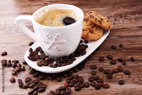Coffee cup with chocolate cookies and coffee beans on wooden background