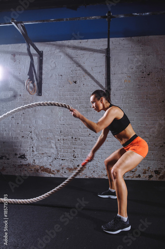 vertical photo of side view athletic woman wearing red pants and black top doing some cross fit exercises with battle rope indoor