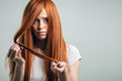 Sad redhead girl holding her damaged hair looking at camera
