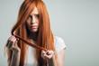 Sad redhead girl holding her damaged hair looking at camera