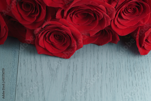 red-roses-on-light-blue-wood-background