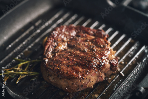 Keuken foto achterwand Steakhouse cooking rib eye steak with herbs on grill pan