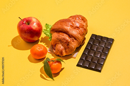 Plakat The apple, chocolate and croissants on yellow background