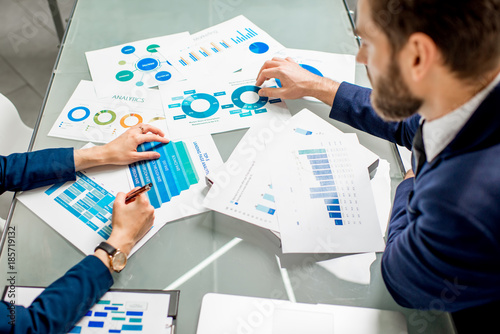 Marketer or analityc manager team working on paper charts at the table. Image focused on the documents