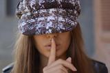 Chica joven con gorra y haciendo el gesto de silencio - 185730130